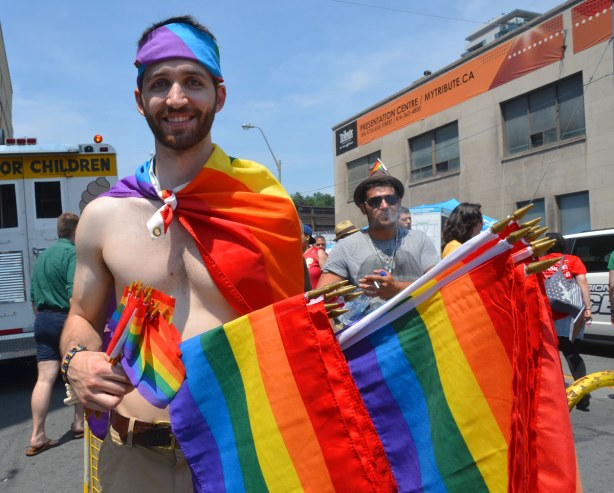 A man is wearing a rainbow flag like a cape, and he has one wrapped around his head like a headband.  He is selling large and small sized rainbow flags.  He is topless otherwise