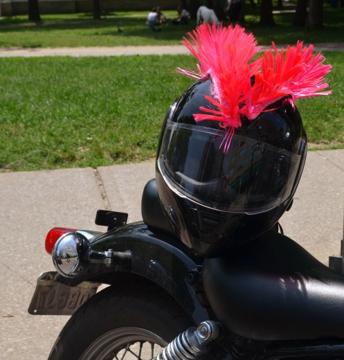 A black helmet has two lines of pink fringe glued on the top it that make it look like a Mohawk hair cut.  The helmet is sitting on the seat of a black motorcycle.