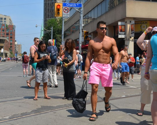 A good looking, very fit, man wearing just a pair of pink shorts and a pair of sandals is walking down the street.
