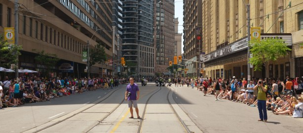 two lone photographers stand in a street that has no traffic.  Crowds are on the sidewalks on either side.  They are sitting, waiting for a parade to come past