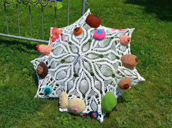 A lacy umbrella decorated with crocheted 3D breasts in different colours, probably life sized.