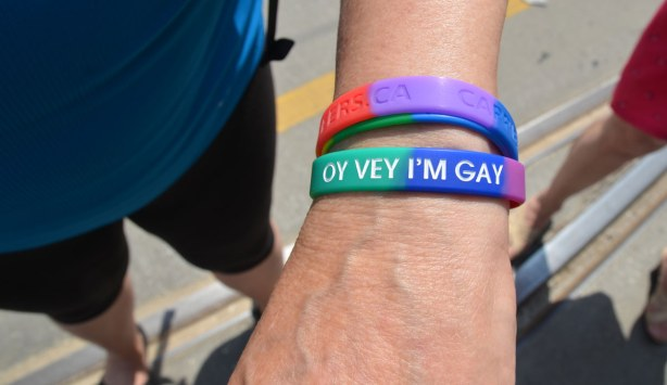 A multicoloured bracelet on a wrist.  The bracelet says, Oy Vey I'm Gay.