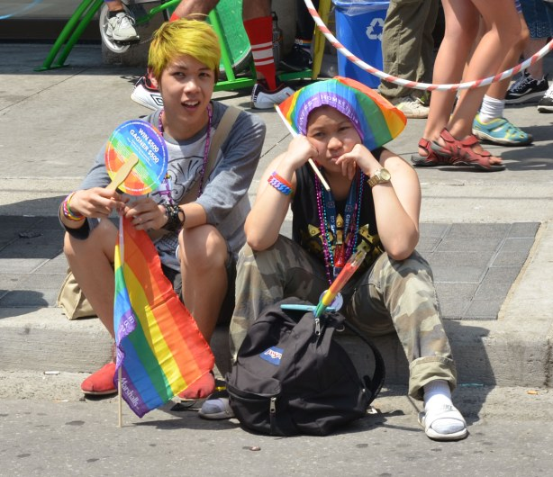 Two guys are sitting on the sidewalk.  One has dyed his hair yellow and he's carrying a rainbow flag.  The other is resting his chin on his hands, and his elbows on his knees.  He has his rainbow flag draped over his head and he looks very bored.