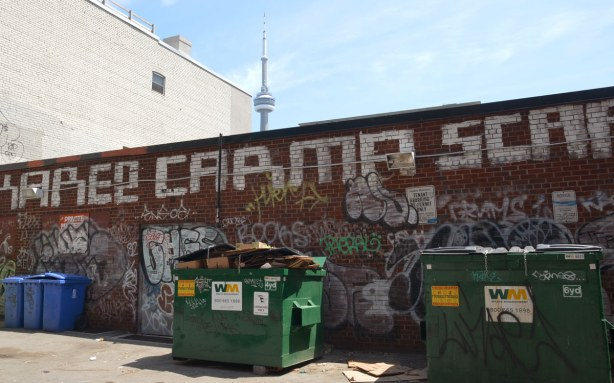 graffiti on a brick wall on Bulwer St., with the CN tower behind in the distance