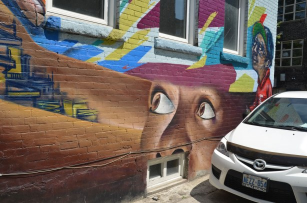graffiti on a brick wall on Bulwer St., big white eyes on a brown face looking up towards the sky.  A white Hyundai is parked beside it.