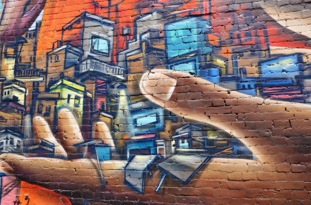 detail of graffiti on a brick wall on Bulwer St., a large brown hand is holding miniature size city buildings in blues and purples