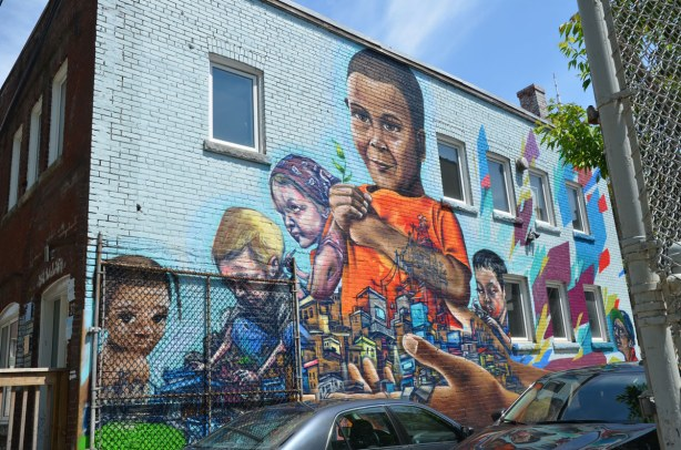 graffiti on a brick wall on Bulwer St., children including a larger than life sized boy wearing an orange T-shirt