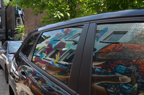reflections of a mural in the windows and side panels of a black car