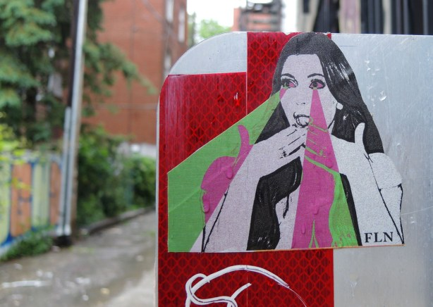 little people graffiti, sticker of a woman holding her hands over her mouth.  rays of green and pink are coming from her eyes.  FLN, or futur lasor now, is the name on the bottom right corner of the sticker