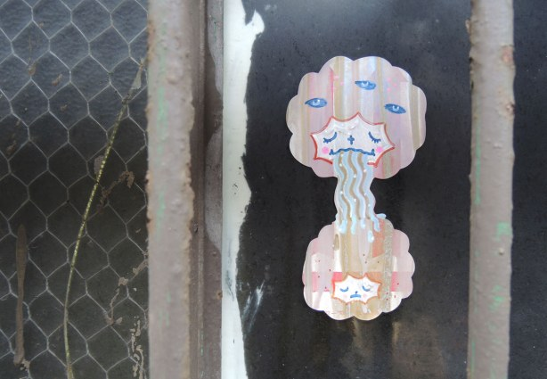 little people graffiti, sticker of two girls' heads.  They have puffy pink hair.