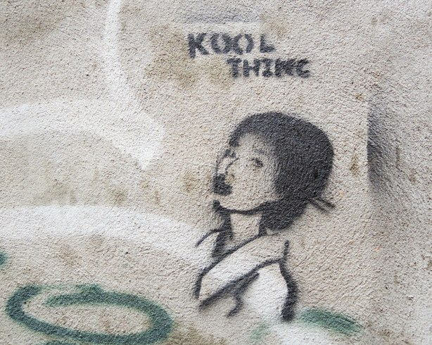 little people graffiti, black line drawing on grey concrete of a girls' head in profile.  The eords Kool Thing are written abover her head.