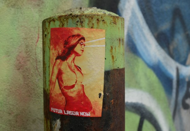 little people graffiti, sticker of a woman from the waist up in oranges and yellows, on a greenish metal post.