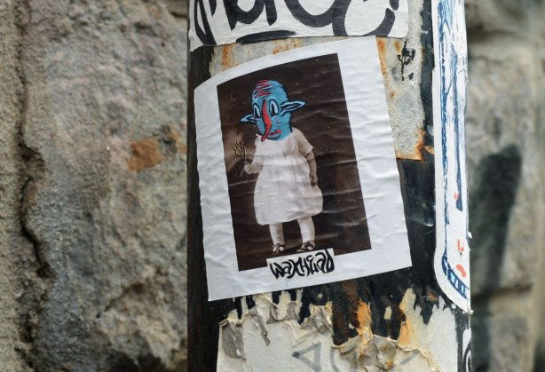 little people graffiti, sticker, waxhead is the name on the sticker, a funny looking person-like creature with a blue head