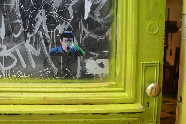 little people graffiti, sticker of Dr. Spock from Star Trek on the window in a door that has been painted a bright yellowish green colour
