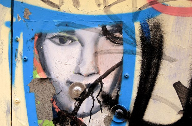 little people graffiti, sticker of a woman's face.  A blue triangle has been painted around it