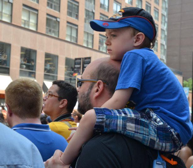 a boy is sitting on his father's shoulders