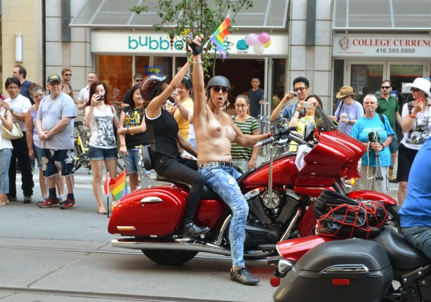 Two women on a red motorcycle.  The one in front is topless and wearing a black helmet.  She has her fist in the air.