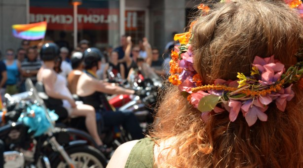 In the foreground of the photo is the back of a woman's head.  She has long wavy reddish hair and she is wearing a garland of flowers in her hair.  In the background are motorcycles in the parade.
