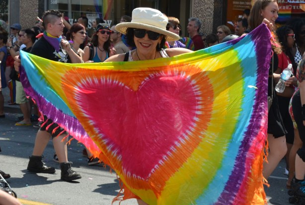 A happy looking woman holding up a large rainbow coloured scarf that has a bright red heart in the middle of it