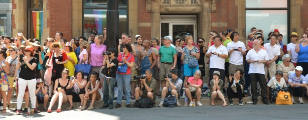 A crowd of people are watching the parade from the sidewalk.  Some are sitting on the kerb and some are standing behind.