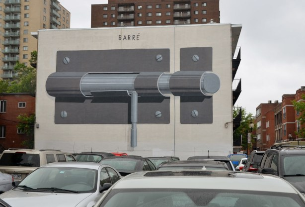 large mural of a sliding lock on the side of a building by a parking lot that is full of cars - only the roofs of the cars are in the picture