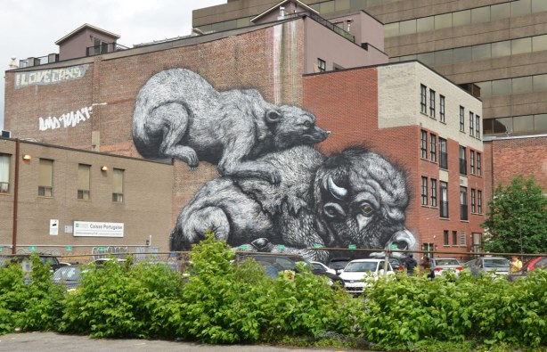 mural painted on the side of a building in Montreal, a very large mural of two animals in black and white