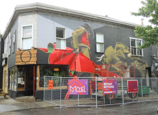 mural painted on the side of a building in Montreal showing a bullfighter with his red cape, and a bull charging at the cape.  Bryan Beyung is the artist.