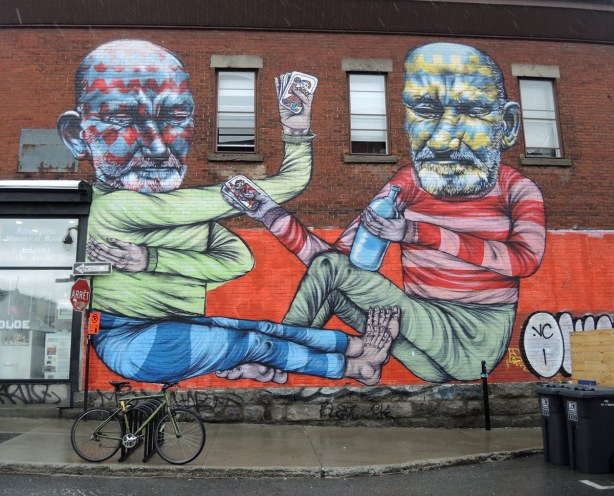 A mural on the side of a brick building in Montreal, a painting of two bearded men playing cards and drinking beer.