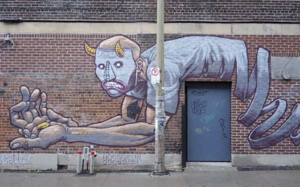 mural of a man lying over the top of a real door.  He is on his elbows on one side of the door.  He doesn't have legs though,  instead a long coiled something is where his legs should be.