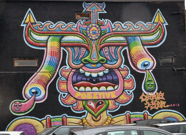 multicoloured abstracted face with head piece.  mouth wide open showing tongue and teeth