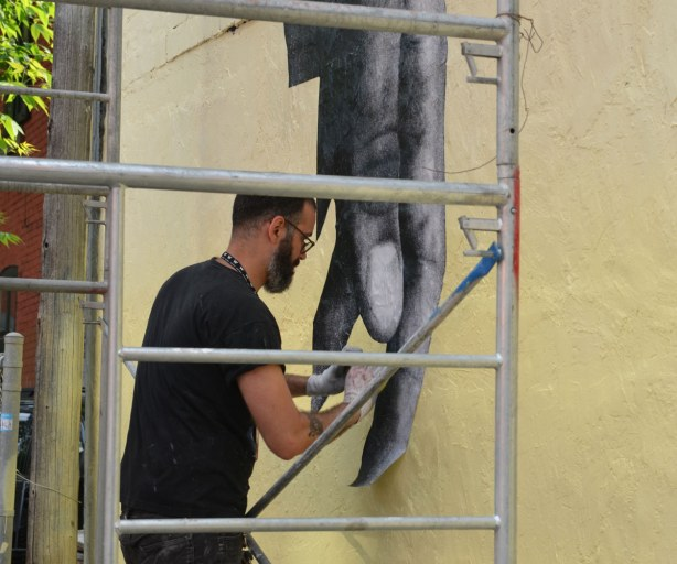 Street art of large hands that have been printed on paper and then pasted to a wall.  The artist is in the process of gluing a finger to the yellow wall.