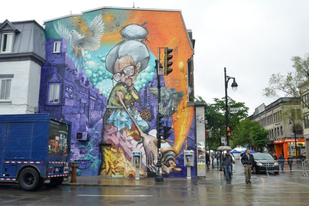 large mural on the side of a two storey building in Montreal.  A painting of an old woman with a spray can of paint, looking like she's painting the sidewalk.