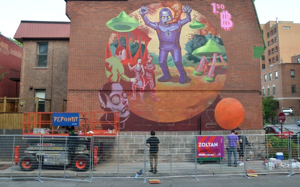 a large mural on the side of a red brick wall in Montreal.  A purple robot like monster is the central figure in the mural by the artist Zoltan
