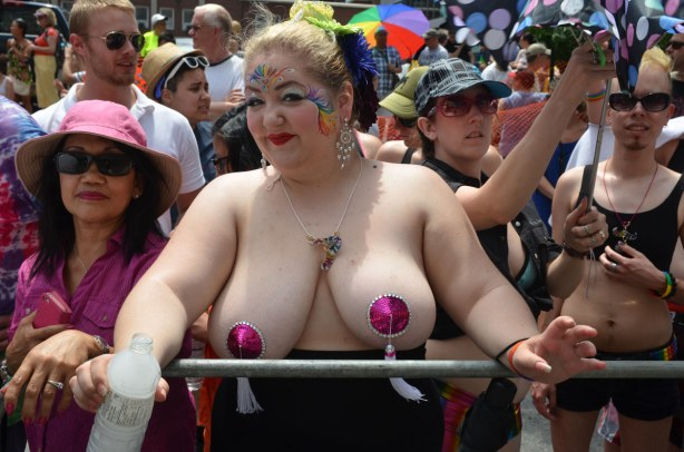A woman with very large and almost bare breasts.  Her face is decorated