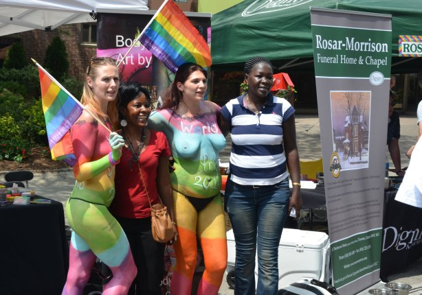 Two topless women are painted in big rainbow colours.  Two clothed women are posing for a photo with them.