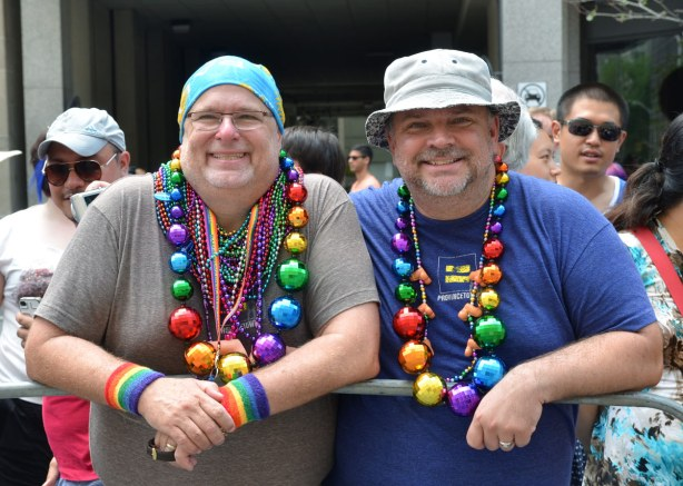 Two men are standing beind, and leaning on, the barricade.  They are wearing multicoloured beads, incuding some very big beads that look more like balls for a Christmas tree