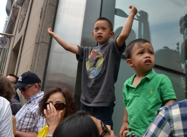 Two boys are standing on a window ledge so they are above a crowd of people.  The small boy doesn't look too happy.