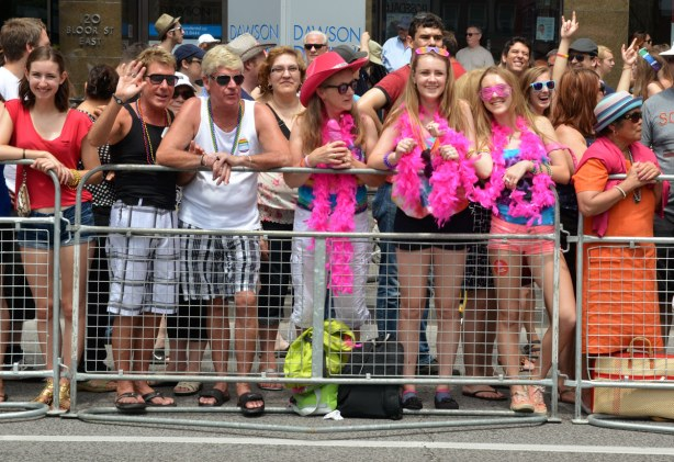 A group of people are standing behind metal barricades waiting for the parade to start,  some are waving and some are smiling.  A group of three girls are wearing pink boas.