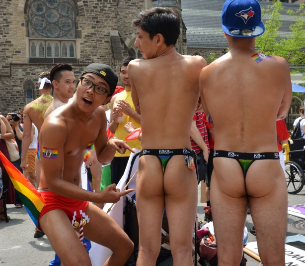 One guy in red underpants (with Christmas bells attached to the front) is pointing to the bare bottoms of his two male friends.  He is making an exaggerated facial expression of surprise and shock.