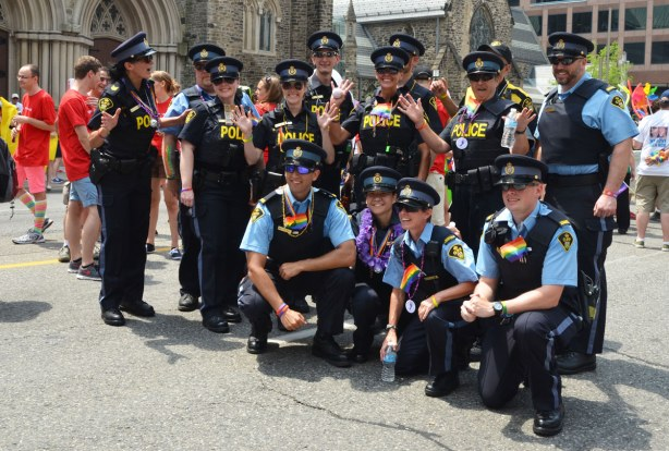 A group of policemen and policewomen pose for a group shot before the pride parade