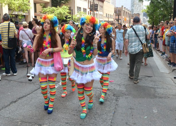 a group of four girls wearing rainbow curly wigs, frilly short skirts and rainbow striped socks are walking up the street between two rows of parade watchers