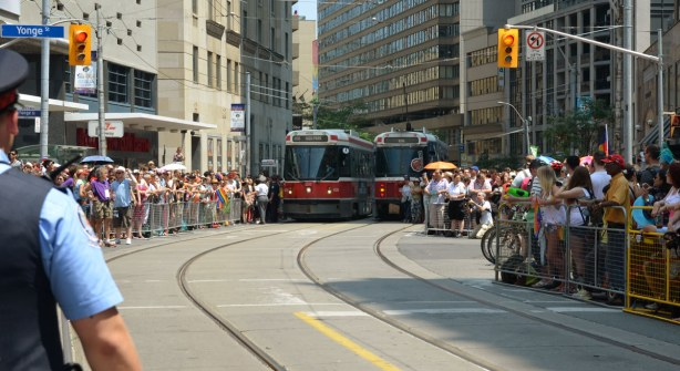 streetcars at the intersection of Yonge & College, all corners are packed with people
