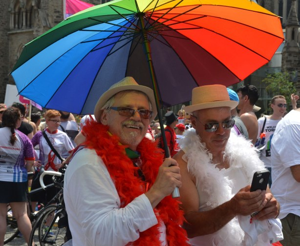 Two older men dressed in white are under a rainbow striped umbrella.  One has a white boa, the other has a red boa.