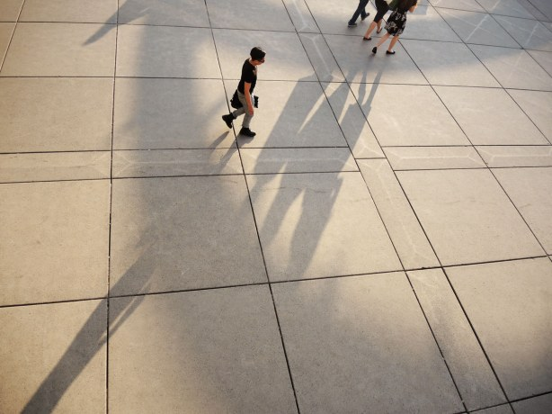 Most of the picture is of shadows on the concrete below.  There are partial shadows of the arches over the fountain at nathan phillips square.  There are also 4 people (or parts of the people) and the long shadows that they cast.