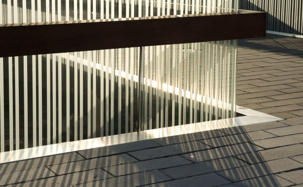 photo of the railing that is made of many vertical white bars.  The railing is not straight.  There are many shadows in the picture, and many patterns, linear and diagonal, made by the white bars and the shadows.