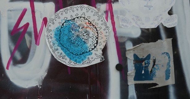 two stickers on a wall.  One is the head of a blue cat.  The other is a lacey looking circular design.