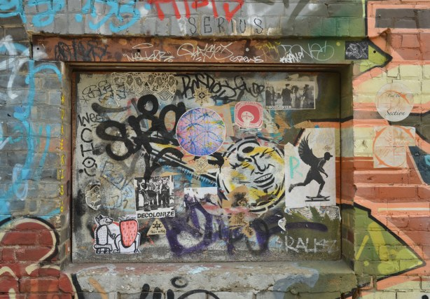 A window space in a brick wall that was covered over a long time ago.  Now there are tags and stickers covering the space as well as graffiti on the walls around the space.