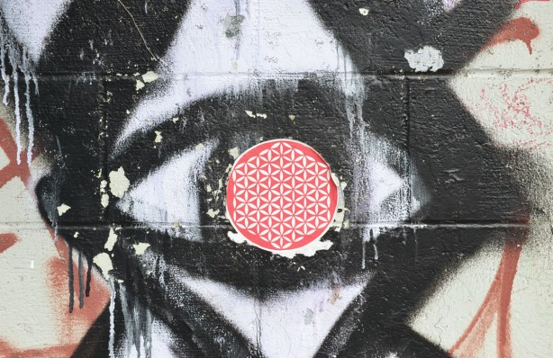 Someone has placed a red & white circular sticker over the iris of an eye that is part of a black and white eye graffiti picture