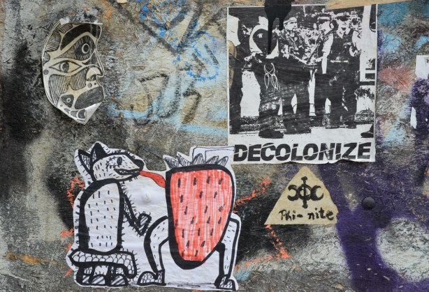 four stickers on a wall.  One is a mask that looks either African or BC First Nations.  One is a hairy dog like creature with a long tongue that is licking a red strawberry with legs.  One has the word 'decolonize' on it along with a picture of a group of men.  The last sticker is just the word 'phi-nite' with a symbol.