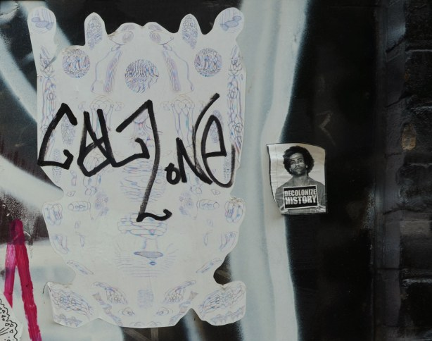 a purple and white sticker that has been defaced by the tag 'calzone'.  Beside it is a sticker that says 'decolonize history' with a mug shot of a man.